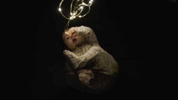 Thumbnail for A Child Plays in the Dark with a Christmas Glowing Garland. Merry Christmas Christmas and Happy New