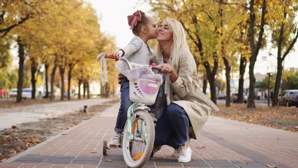 Thumbnail for Little Girl Hugs and Kisses Her Mother While Walking in Park