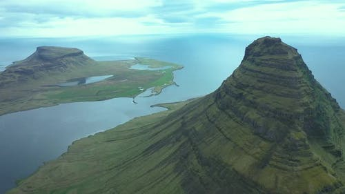 Flying Over Kirkjufell Mountain and the Sea in a Cloudy Day, Iceland