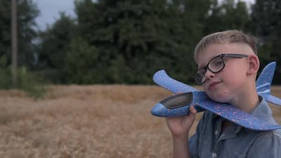 The guy is played with a toy airplane model on a wheat field.