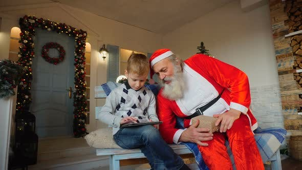 Thumbnail for Happy Boy Receiving Tablet From Santa Claus.