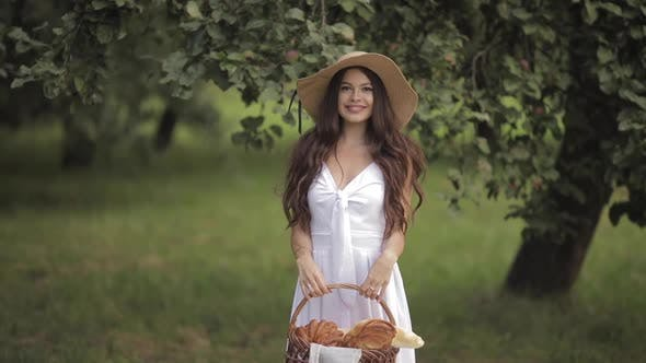 Happy Young Woman in a Straw Hat Walking Ahead