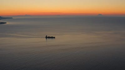 Silhouette of a small transport ship after sunset in Italy