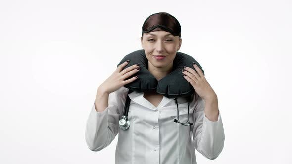 Thumbnail for Sexy Female Doctor Puts on Sleeping Mask, Travel Pillow, Winks and Fall Asleep