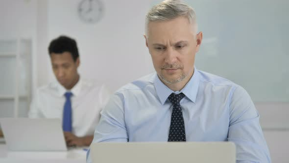Thumbnail for Grey Hair Businessman Looking at Camera in Office
