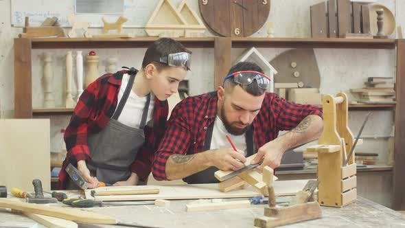 Thumbnail for Male Teacher and His Male Pupil Making By Hand a DIY Wooden Toy
