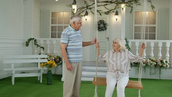 Thumbnail for Senior Couple Together in Front Yard at Home. Man Swinging Woman. Happy Elderly Pensioners Family