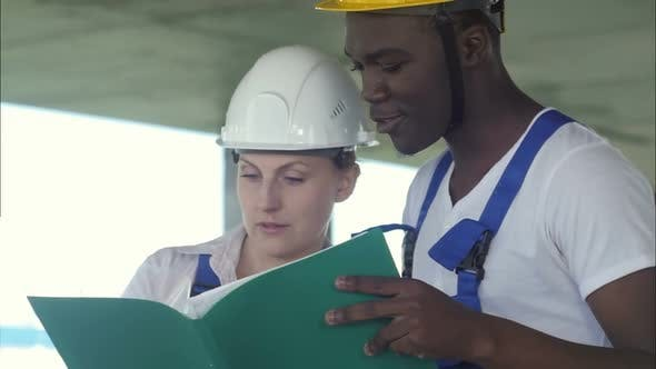 Thumbnail for Afro-american Architect and Female Technician at Construction Site Reviewing Office Blueprints
