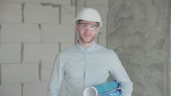 Thumbnail for Young engineer-architect with  blueprints looks at the camera