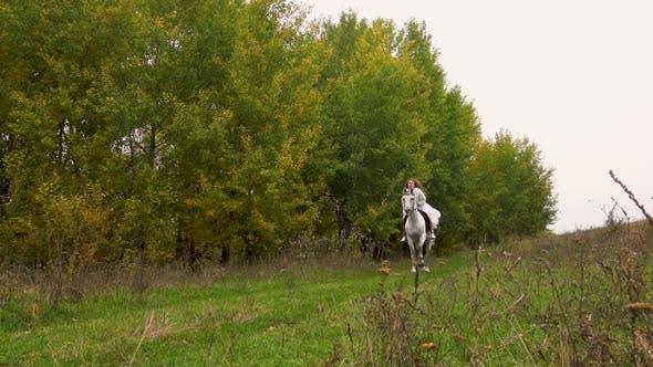 Thumbnail for Langhaarige Frau in weiß Kleid ist Reiten Pferd entlang Holz