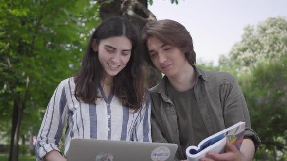 Cover Image for The Male and Female Students in Casual Clothes Sitting at the Bench, Girl Holding Laptop and Boy Has