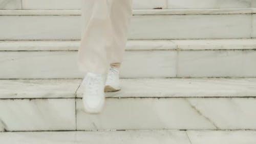 Woman In Sneakers Walking Down Marble Steps