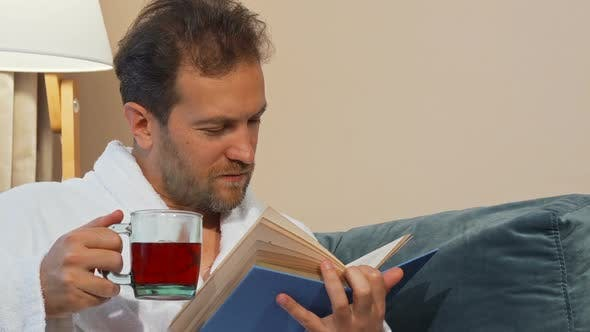 Mature Man Having Aromatic Hot Tea, Reading a Book at Home, Wearing Bathrobe 1080p