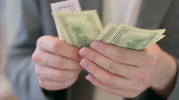 Close Up of Hands of Young Man Counting Dollars