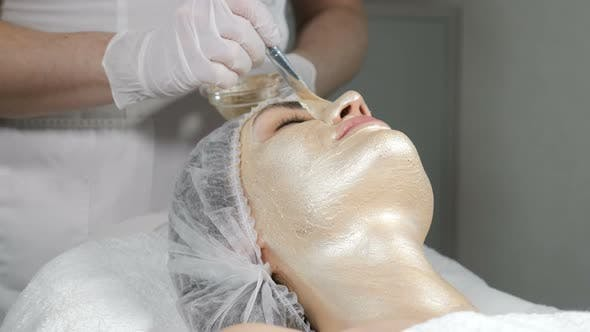 Beautician Applying Beauty Mask on Beautiful Female Girls Face. Cosmetic Golden Mask on Face