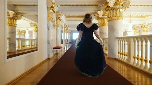 Woman in an Elegant Dress Walks Along the Golden Corridor of the Theater