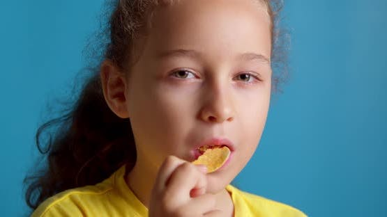 Cute Little Funny Child Little Girl Eat Potato Chips Kids Take Chips and Have Fun Kids Eat at the