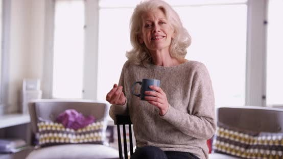 Thumbnail for Happy elder woman holding coffee mug snapping her fingers smiling inside home