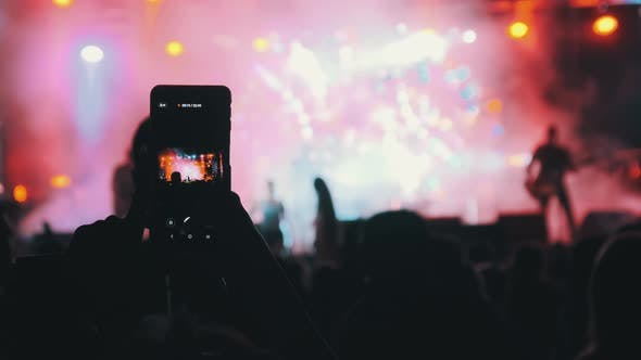 Thumbnail for Woman Hands Silhouette Recording Video of Live Music Concert with Smartphone