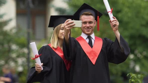Thumbnail for Graduate Students in Academic Dresses Taking Selfies After Graduation Ceremony