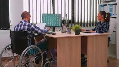 Paralysed Financial Expert Sitting in Wheelchair Analysing Economy
