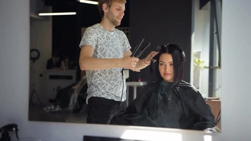 Hairdresser Straighten Brown Hair To Woman Using Hair Iron in Beauty Salon