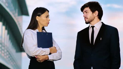Business Man and Woman Having a Casual Talk Outdoors