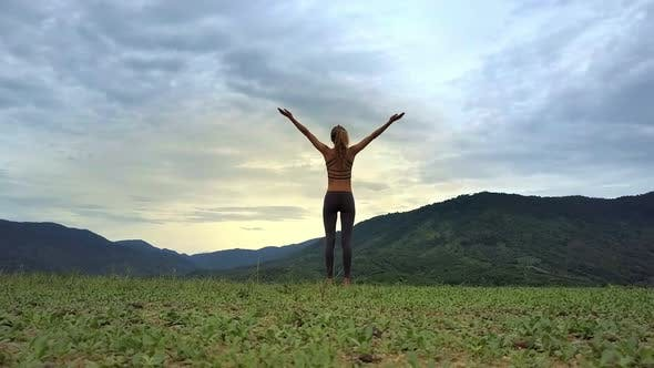 Thumbnail for Drone View Girl Stands in Yoga Pose Against Hilly Landscape