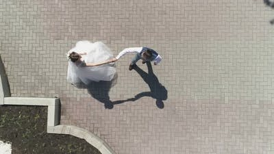 Top down aerial view of wedding couple dancing in a park 23