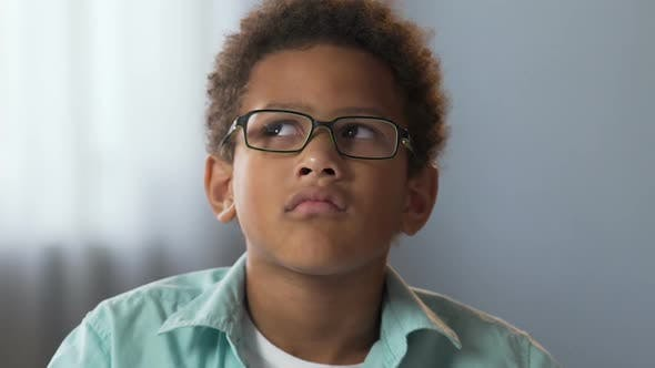 Thumbnail for Mixed-Race Male Kid in Glasses Thinking Carefully Thoughtful Face Expression