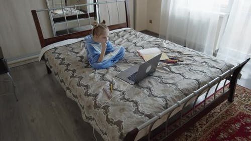 Vorschulmädchen in Kegurum mit Laptop im Zimmer studieren