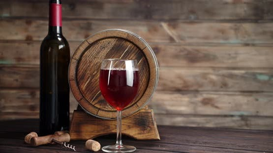 A Glass of Red Wine Slowly Rotates on the Table. On a Wooden Background.