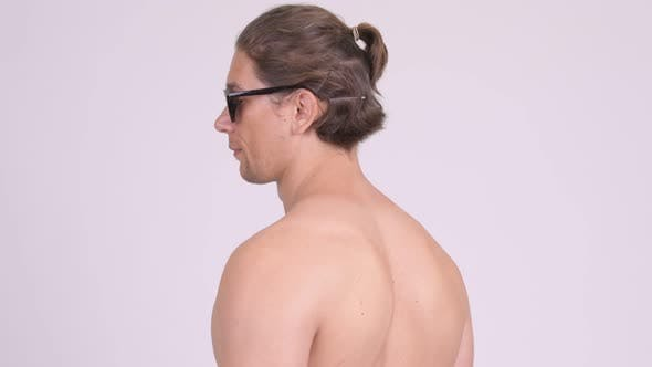 Cover Image for Rear View of Muscular Shirtless Man Looking Back and Removing Sunglasses