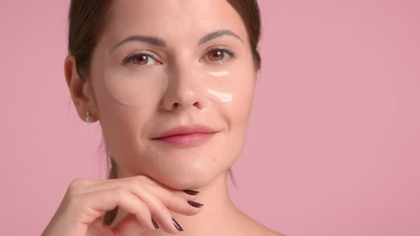 30s Brunette Woman Wears a Decollete Top with Ideal Skin in Studio on Pink Background