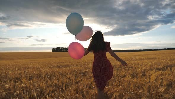 Rear View of Happy Girl in Red Dress Running Through Golden Wheat Field with Balloons in Hand at