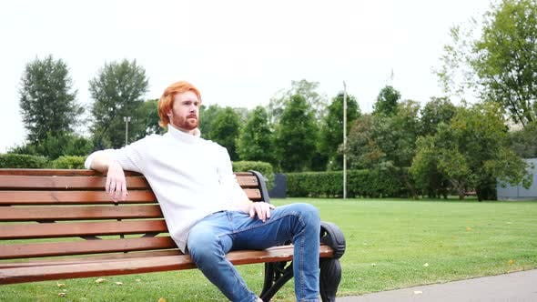Thumbnail for Man Sitting in Park on Bench, Red Hairs and Beard