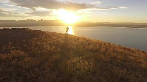 Flying towards man overlooking lake at sunset in golden landscape