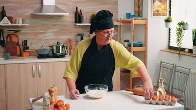 Woman Breaks Egg Above White Flour