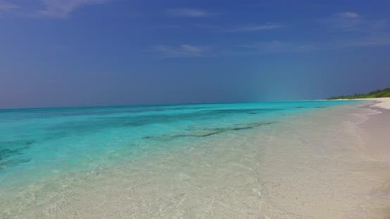 Wide angle birds eye abstract view of a white paradise beach and aqua blue ocean background in colou