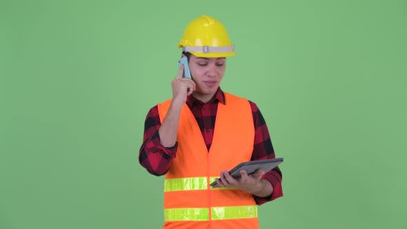 Thumbnail for Happy Young Multi Ethnic Man Construction Worker Talking on the Phone While Using Digital Tablet