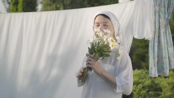 Thumbnail for Attractive Senior Woman with White Shawl on Her Head Sniffing Daisies Looking at Camera Smiling