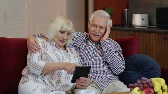 Senior Pensioner Couple with Digital Tablet Pc Computer at Home. Resting on Sofa in Cozy Living Room