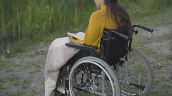 Thumbnail for Back Angle View of Positive Disabled Young Woman Reading Book Outdoors. Confident Caucasian Lady on
