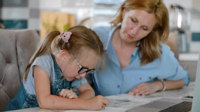 Little Cute Daughter Doing Homework with Mother