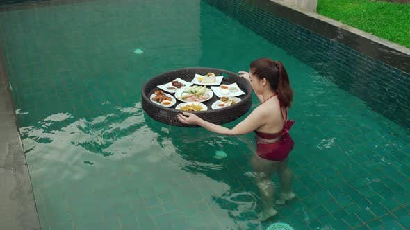young woman enjoying with floating food in swimming pool