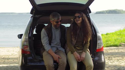 Romantic Tourists Sitting in Car Trunk and Chatting on Lakeside