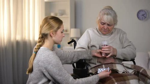 Young Lady Bringing Painkillers to Grandmother Feeling Stomach Ache, Health-Care
