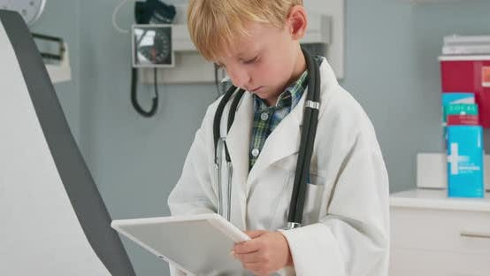 Thumbnail for Close up of a cute little boy dressed up as a doctor using a tablet computer