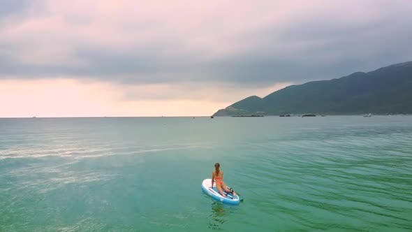 Thumbnail for Waves Carry Blond Woman on Paddleboard To Open Ocean