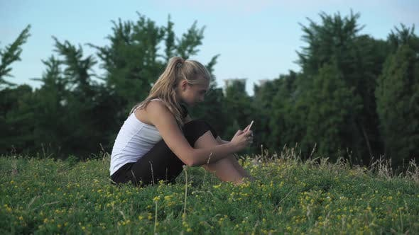 Thumbnail for Young Girl Shirt Sits on a Hill and Gaining a Message on Your Mobile Phone.